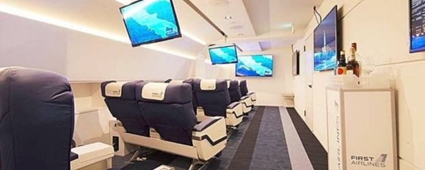 Grounded travellers sit in first or business class seats in a mock airline cabin where they are served in-flight meals ...