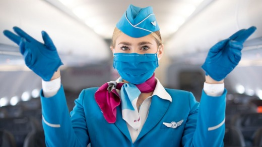 A Eurowings flight attendant wears a mouth and nose protector and gloves.