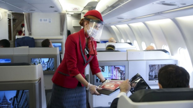A stewardess wearing a face shield serves business class travellers.