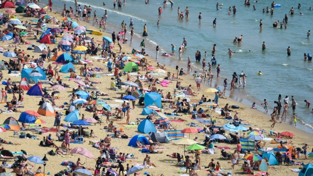Tourists flock to the beach in Bournemouth, England, earlier this month. British citizens have expressed anger over ...