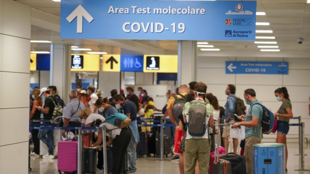 Vacationers arriving in Rome from four Mediterranean countries line up with their suitcases at Rome's Leonardo da Vinci ...