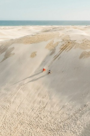 Couple enjoying a sandboarding experience at Stockton Sand Dunes located in the Worimi Conservation Lands.