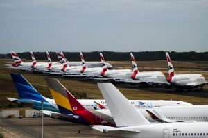 A fleet of Airbus SE A380 passenger aircraft, operated by British Airways, sit parked near other grounded jets at ...