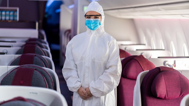 A flight attendant wearing protective equipment on board Qatar Airways. Akbar Al Baker, chief executive of the airline, ...