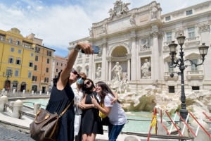 People take selfies in front of Trevi Fountain.