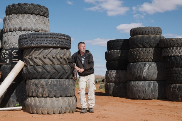 The owner of the Mad Max 2 Museum in Silverton, Adrian Bennett. The tyres  are part of the entrance that replicates one ...