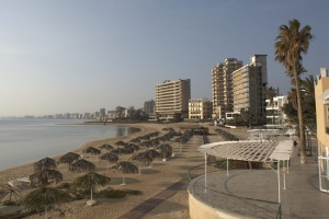 Beach umbrellas on Palm Beach bordering the ghost town of Varosha, abandoned during the Turkish invasion of 1974. one ...