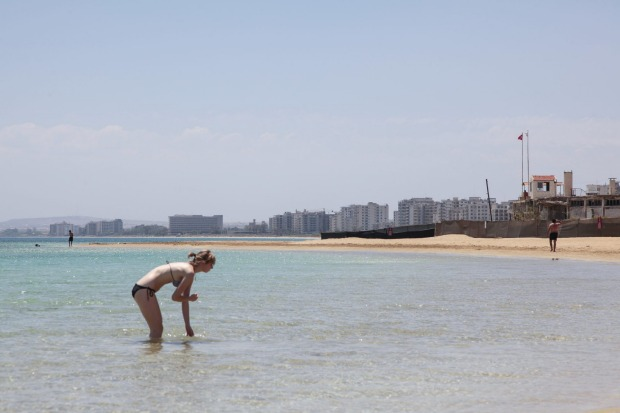 A tourist enjoys the beach in front of the 'Forbidden Zone' of Varosha.