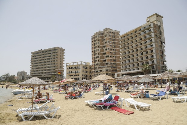 Tourists lie on a public beach next to decaying hotel buildings that stand inside the 'Forbidden Zone' of Varosha district.