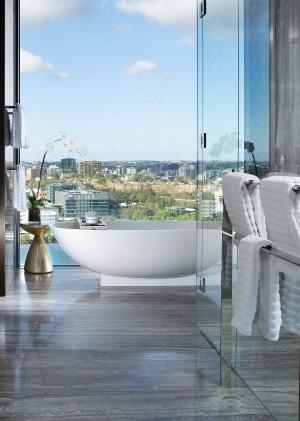 The master bedroom has an en-suite with double rain showers and a stand-alone bath looking over Brisbane's skyline ...