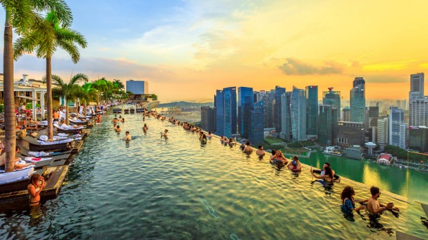Singapore - May 3, 2018: Infinity Pool at sunset of Skypark that tops the Marina Bay Sands Hotel and Casino from rooftop ...