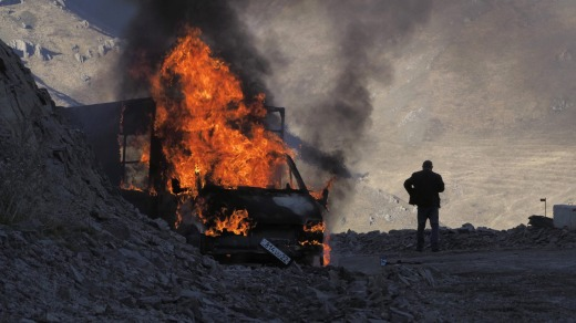 A man stands near his burning car which caught on fire during the climb along the road to a mountain pass, near the ...
