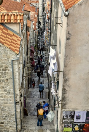 Tourists walk on a typical alley in Dubrovnik, Croatia. Dubrovnik is one of the oldest towns at the Adriatic Sea, and it ...