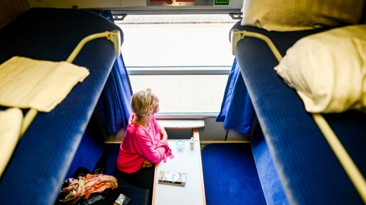 A woman travels in a compartment of a night express train in Westerland, Germany.