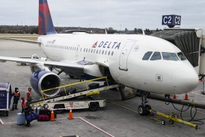 Two people and their dog have leapt from a Delta plane at New York's LaGuardia Airport.