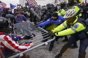 Trump supporters try to break through a police barrier outside the Capitol Building in Washington DC.