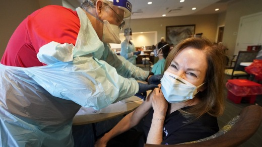 Healthcare worker Pam Peter, right, prepares to receive her second round of a COVID-19 vaccine in Florida.