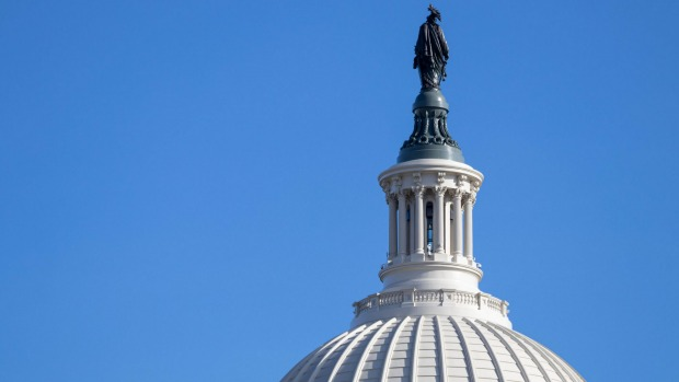 What is the name of the bronze statue that sits atop the US Capitol building's dome?