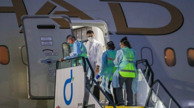 Bio security staff board a plane carrying tennis players and support teams upon its arrival in Melbourne last month. The ...
