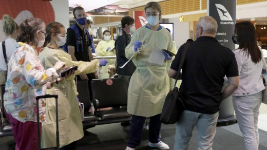 Health workers screen passengers arriving from Melbourne at Sydney Airport.