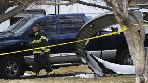 A firefighter walks past a large piece the United Airline plane's engine housing that fell in the suburbs of Denver.