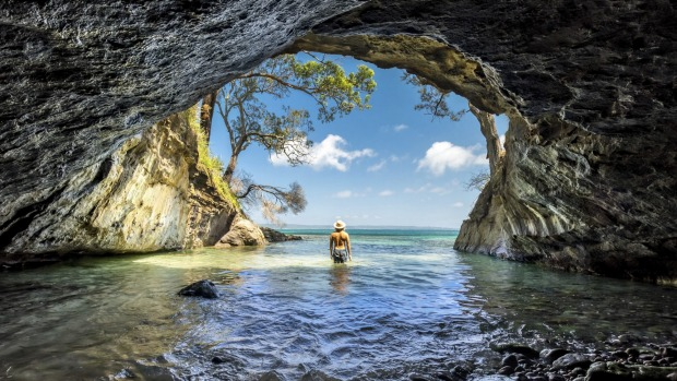 Man enjoying the sun from a sea cave in Jervis Bay, NSW.