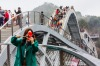 Tourists walk on Ruyi Bridge at Shenxianju Scenic Area in Taizhou, Zhejiang province China. When images of the bridge ...