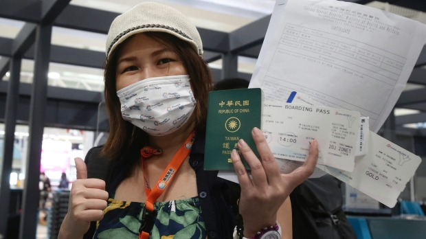 Kuo Yitting, one of the first group travelling to Palau, shows her boarding pass and virus test before leaving Taiwan on ...