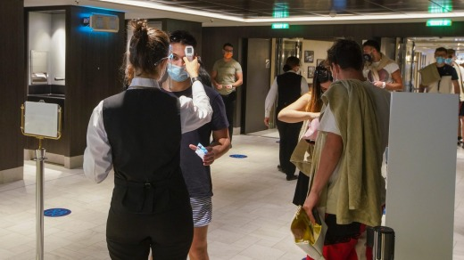 Passengers have their temperature checked as they enter a restaurant on board.