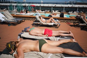 Passengers enjoy the sun by a swimming pool on board the MSC Grandiosa.