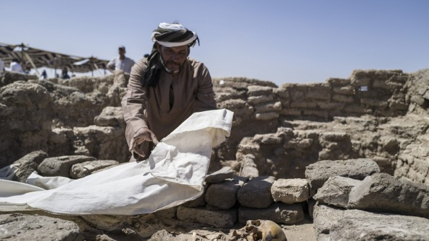 A worker covers skeletal remains found at the site of a 3000 year-old lost city in Luxor, Egypt.