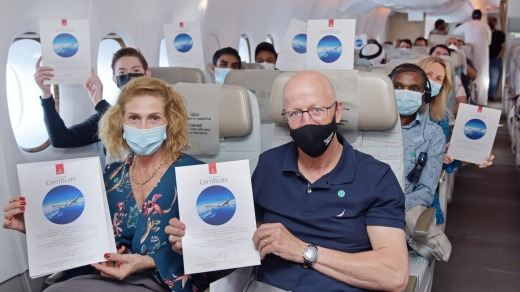 Passengers display their commemorative certificates on board the Emirates flight.