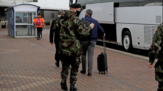 A passenger is escorted to the Crowne Plaza hotel for quarantine in Dublin, Ireland.