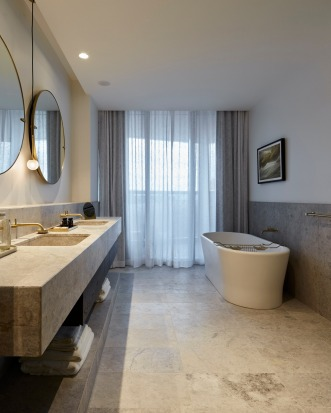 Radiance River View Suite's marble bathroom with bathtub.