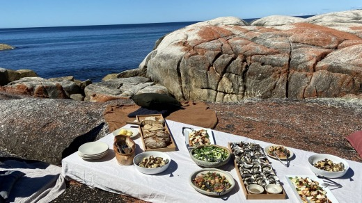 Lunch on the rocks at Tasmania's Bay of Fires with Blue Derby Pods Ride.