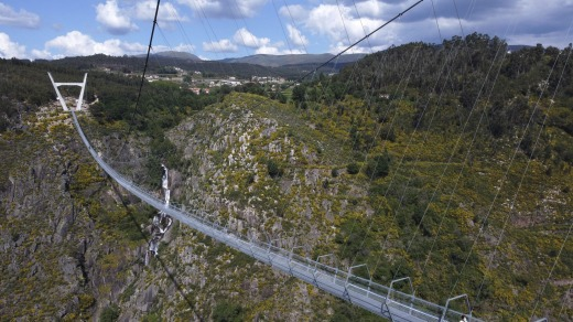 People walk across a narrow footbridge suspended across a river canyon, which claims to be the world's longest ...