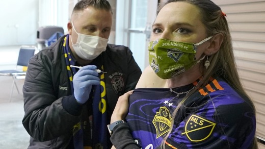 A Seattle Sounders soccer team fan gets a COVID-19 vaccine injection at the Lumen Field sports stadium's concourse, ...