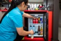 A staffer stocks the minibar at Ovolo Woolloomooloo. Ovolo hotels provide minibar items free of charge.