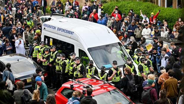 Protestors block a UK Home Office van to stop it from leaving Glasgow on Thursday.