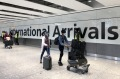 Passengers arrive at London's Heathrow airport. The UK has introduced a 'traffic light' system for dealing with arrivals ...