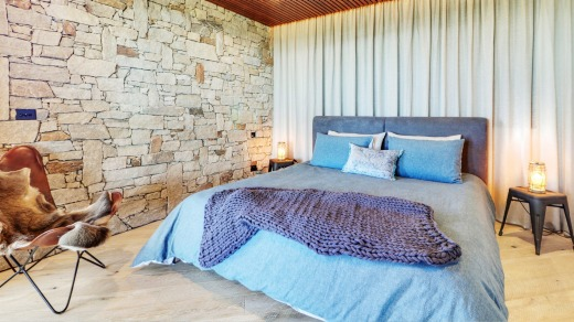 Snuggle under luxe linen in a king bed in the cosy master bedroom with a beautiful rock feature wall that evokes chalet ...