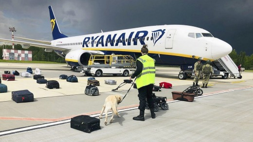 Security use a sniffer dog to check the luggage of passengers on the Ryanair plane after it landed in Minsk.
