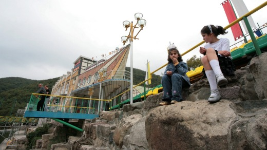 Two girls sit by the ship-shaped Eclectic Hotel in Vank.