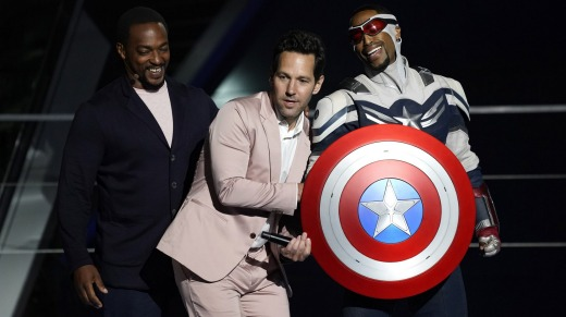 Anthony Mackie, left, and his character Captain America, right, appear on stage with Paul Rudd at the Avengers Campus ...