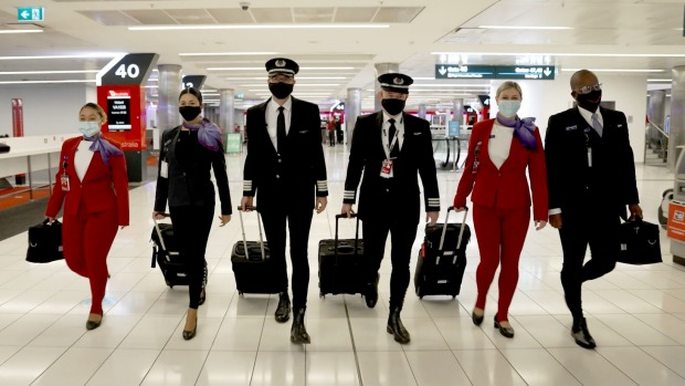 The Virgin Australia pilots and crew model the long johns before the flight.