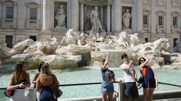 Tourists throw their coins into Rome's Trevi Fountain in June as restrictions were lifted across Italy.