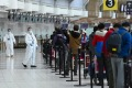 Passengers line up to check in for an international flight at Pearson International Airport in Toronto.