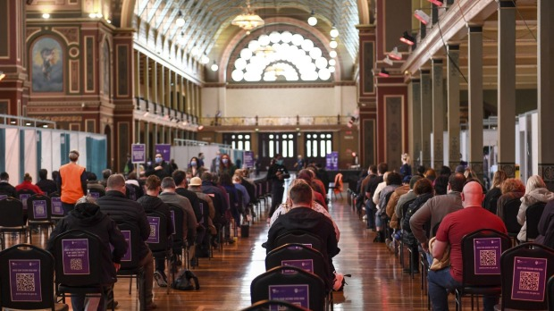 Victorians sit during the 15 minute waiting period after getting their vaccines at the Royal Exhibition Building in ...