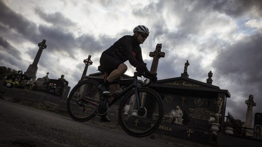 A cyclist rides through the Melbourne General Cemetery, Parkville.