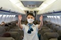 Portrait of a flight attendant showing the emergency exit in an airplane wearing a facemask before takeoff - traveling ...